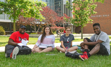 UCBA students sit on the grass.