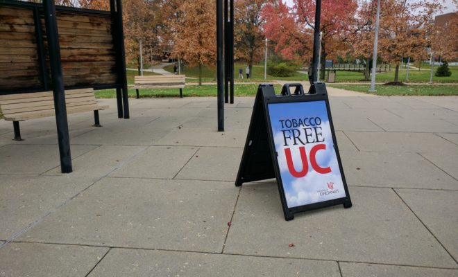 A Tobacco Free UC sign sits near an entrance to Muntz Hall.