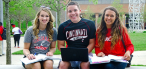 Three students sit facing the camera with books and a laptop.