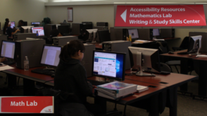 A photograph of students in the computer concourse in Muntz Hall with signs for the Math Lab, Accessibility Resources, and the Writing and Study Skills Center visible.