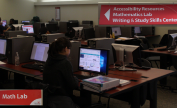Image of a UCBA computer lab with signs to support services.