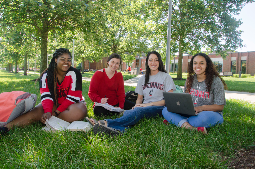 a group of four students sits on the grass on the UCBA campus