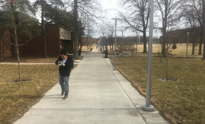 A person walks along a sidewalk on the UCBA campus.