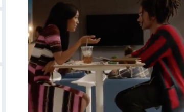 Two characters talk at a table with food