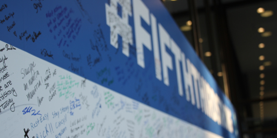 A blue and white poster with signatures