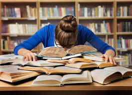 A student buries her head in a pile of books.