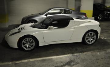 A white Tesla in a parking garage