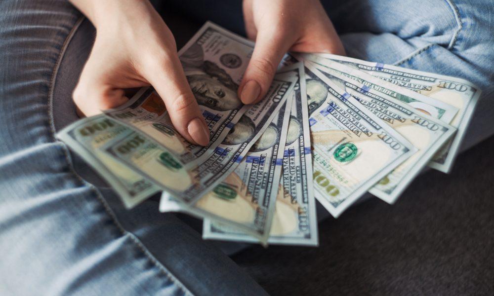 Girl holding one hundred dollar bills