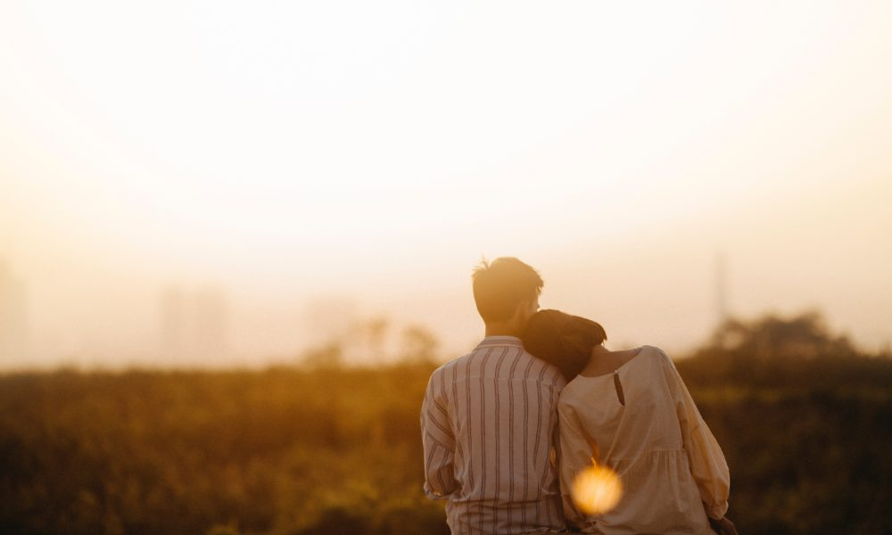 A couple leaning against each other facing away from the camera with a blurred field behind them