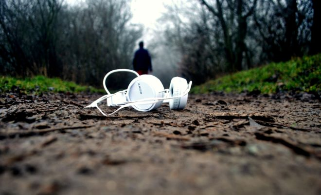 Headphones on a dirt path with nature and a person in the background