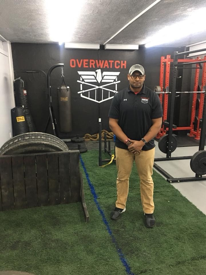 "gym equipment, the word ""overwatch"" on the wall, and Robert Merriweather"