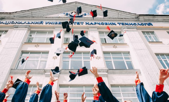 Graduating class throws caps in air