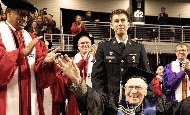 grandson stands behind his grandfather at graduation