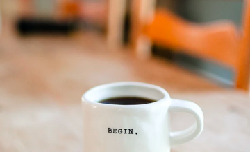 "A white coffee mug with the text ""begin."""